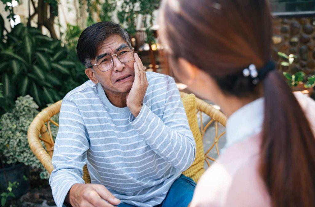 senior man holding jaw and talking to nurse
